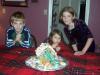 Wyatt, 'Bella, and Madi pose with their gingerbread house