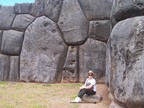Susan dwarfed by the immense stones in walls at Sacsayhuaman, outside Cusco