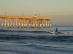 Catching a wave at sunset near Johnnie Mercer's pier
