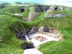 A home at Skara Brae without out its earthen roof and walls. Hearth in the middle. Sleep area beyond. Other homes in the background.