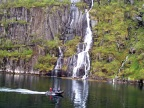 The guides on a zodiac shoot us as we shoot the waterfalls in Troll Fjord