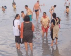 Indian tourists wade in the Dead Sea, Israel