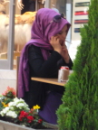 Moderen Moslem Woman in turkey sporting shades, drinking coffee, talking on cell phone, and smoking